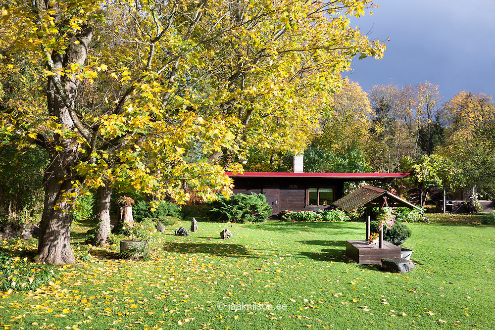 Rural garden with wooden well and sauna in Estonia. Autumn, colourful trees and leaves.
