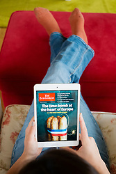 Reading digital edition of The Economist magazine on an iPad mini tablet computer