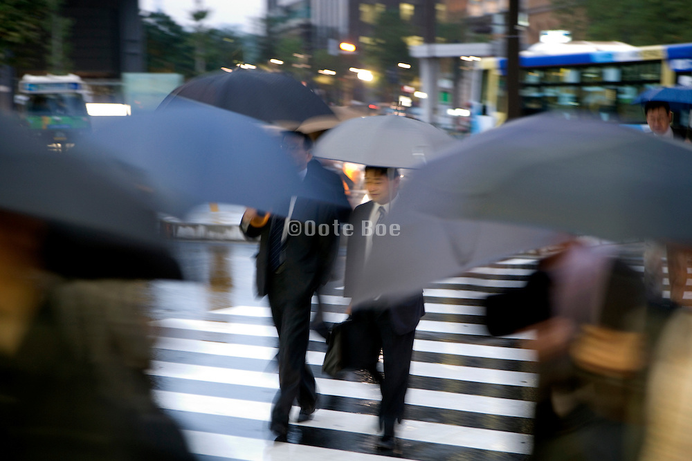 businesspeople walking across a zebra crossing during a rainy day