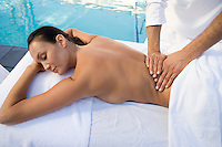 Woman having massage by swimming pool