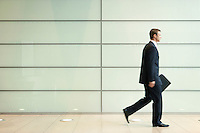 Businessman Striding Down Office Corridor side view