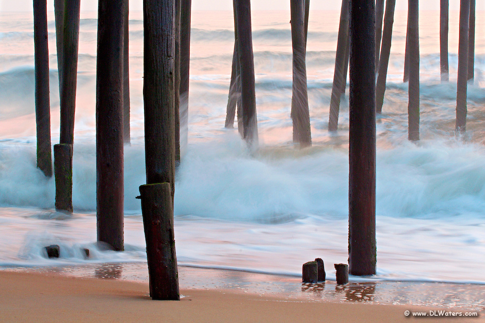 This photograph underneath of Kitty Hawk Pier was taken with a slow shutter speed on a tripod in order to capture the contrast of the soft movement of the waves against the sharp focus of the pilings.
