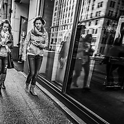Downtown Chicago - two woman looking at cell phones as they walk down the street.