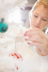 Close up of Young Woman Decorating Christmas Tree