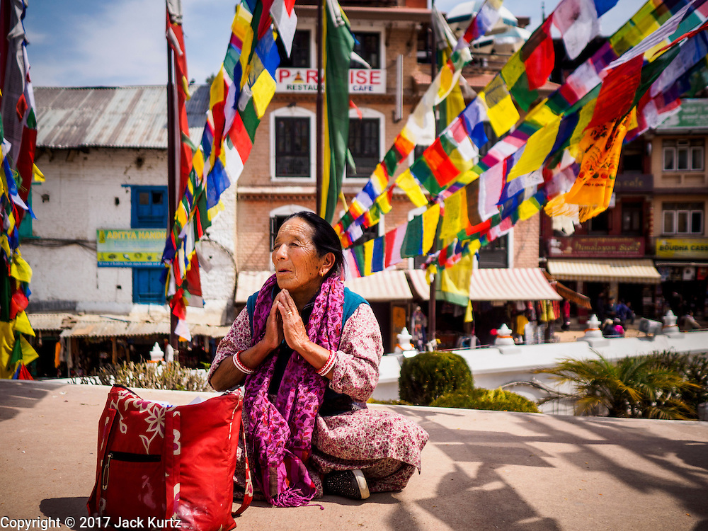 07 MARCH 2017 - KATHMANDU, NEPAL: A Nepalese Buddhist woman prays during the consecration ceremony at Boudhanath Stupa. Boudhanath Stupa, the most important Buddhist site in Nepal and a popular tourist attraction, was consecrated Tuesday in a ceremony attended by thousands of Buddhist monks and Buddhist people from Nepal and Tibet. The stupa was badly damaged in the 2015 earthquake that devastated Nepal. The stupa, which reopened in November 2016, was repaired in about 18 months. The repair was financed by private donations raised by international Buddhist organizations.     PHOTO BY JACK KURTZ