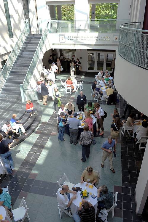 """Kent State Alumni attending the """"Alumni College"""" participate in a museums tour and wine tasting in the atrium in Rockwell Hall."""