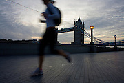 At first light, an early morning jogger runs past Tower Bridge on the South bank of the River Thames in London