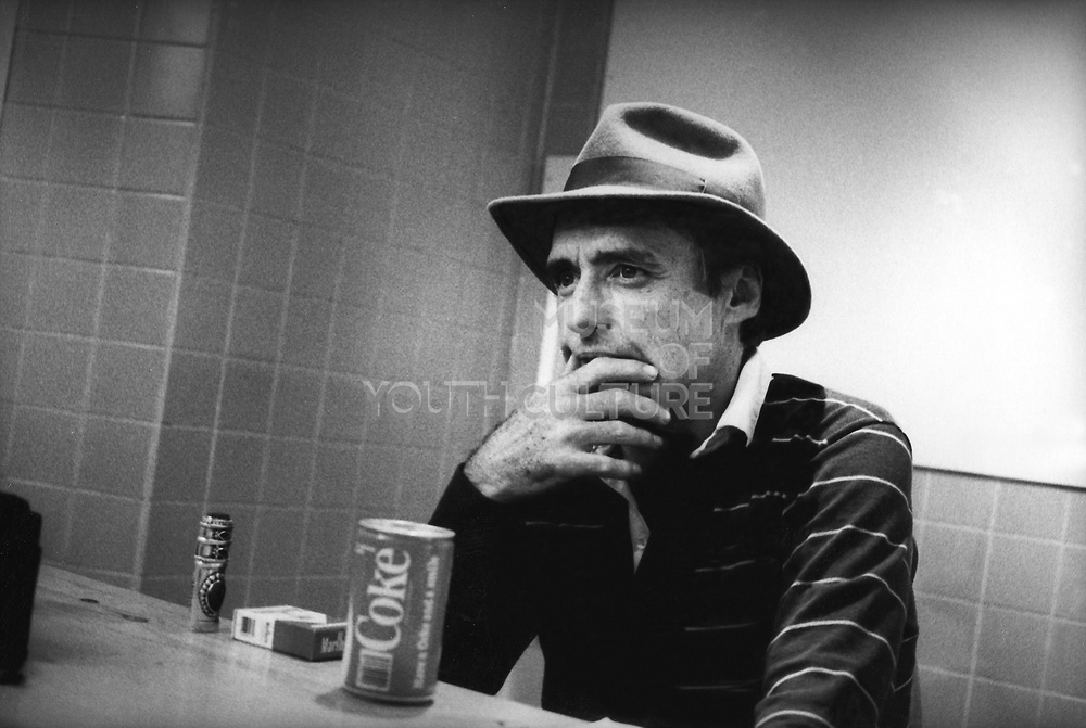 Dennis Hopper sat at a table looking thoughtful, next to a can of Coke, UK, 1980's.