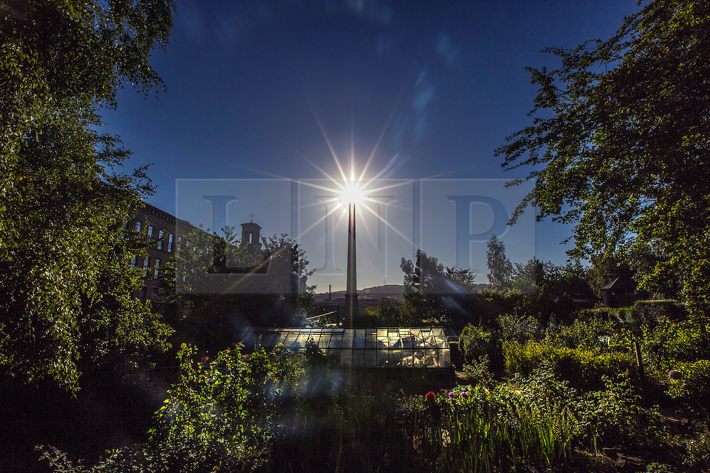 © Licensed to London News Pictures. 25/08/2015. Saltaire, UK. Picture shows the sun sitting above the Salts Mill allotments in the World Heritage village of Saltaire. Yorkshire woke to bright sunshine this morning although a cloudy afternoon is expected. Photo credit: Andrew McCaren/LNP
