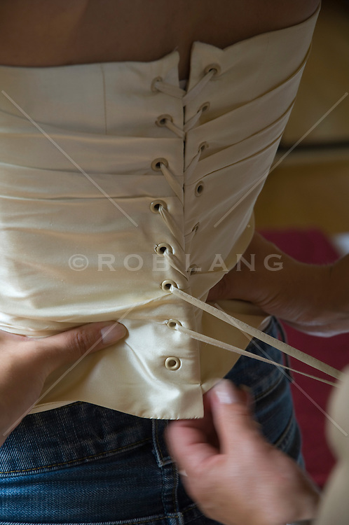 Detail of a corset being tied for a bride in jeans