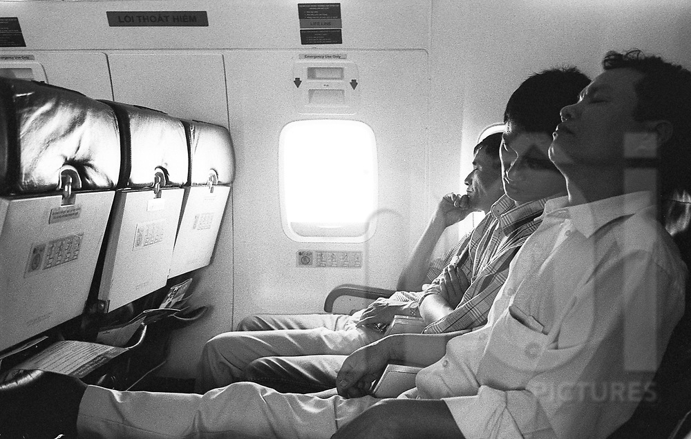 Passengers sleep in their seats abroad a flight bounding to Hanoi, Vietnam, Asia.