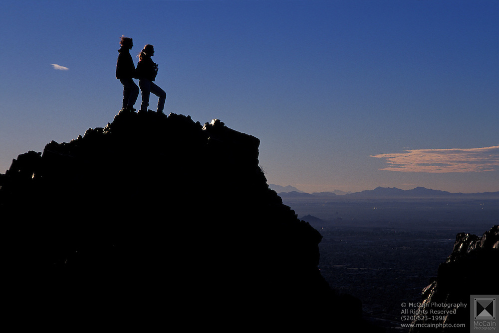 Silhouette of two female hikers enjoying sunrise over Valley of the Sun from Squaw Peak, Phoenix, Arizona..Subject photograph(s) are copyright Edward McCain. All rights are reserved except those specifically granted by Edward McCain in writing prior to publication...McCain Photography.211 S 4th Avenue.Tucson, AZ 85701-2103.(520) 623-1998.mobile: (520) 990-0999.fax: (520) 623-1190.http://www.mccainphoto.com.edward@mccainphoto.com.