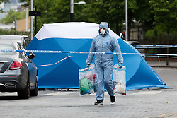 © Licensed to London News Pictures. 27/05/2019. London, UK.  A Police forensic officer near a forensic tent at the crime scene in St Paul's Way, Mile End in Tower Hamlets, where a 23 year old man was stabbed multiple times yesterday, 26th May and died overnight in hospital.  Photo credit: Vickie Flores/LNP