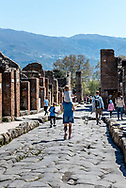 POMPEII, ITALY -  Families find their way through the time-worn streets of  Pompeii on a warm spring day. Ruts in the stone-work avenue reveal where iron-tired carts once passed, while elevated sidewalks and crossing stones show how pedestrians  avoided stepping in the city's wastewater and overflow from dozens of public fountains, which flowed through these corridors.