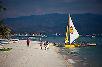 Yellow and white sailing boat near white sand beach on boracay island, Philippines.