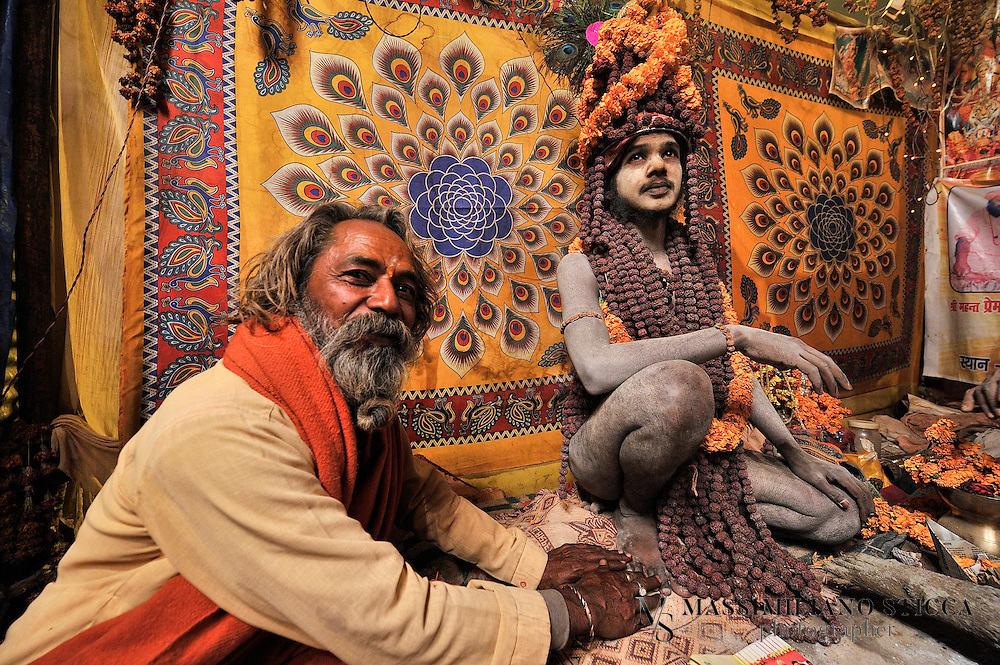 A Sadhu (or Naga Baba) in a tent  in Kumbh Mela near a pilgrim. Sadhu is an ascetic holy man who devotes himself to the goal of moksha or liberation so that soul can overcome the cycle of reincarnation. The Sadhu tradition in India has a long history which can be traced back to the Vedic Age. Such a Hindu ascetic or a monk renounces worldly pleasures in pursuit of higher values of life in order to attain enlightenment. Through strict and hard practice Sadhu detached themselves from  pleasures and pains of human life which makes them indifferent from world and transports them to the metaphysical world..Etymologically Sadhu is a Sanskrit word which means a wise man who renounces the world and all worldly pleasures in quest of spirituality, which ultimately lead them to enlightenment. In order to achieve the zenith of human life they live in caves, temples, forests and hill top, practicing strict code and conduct.