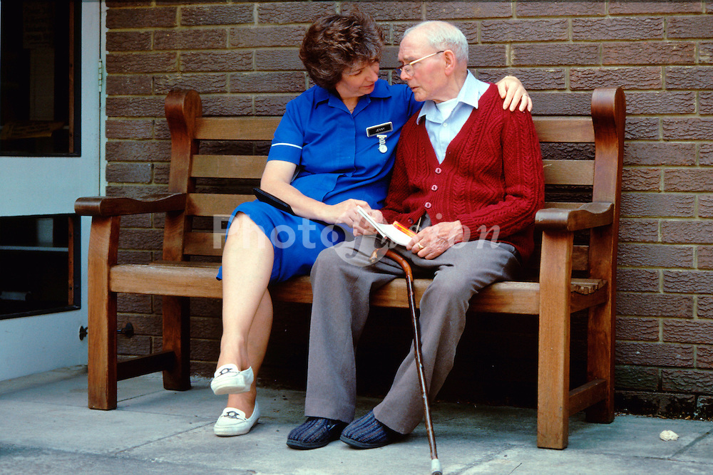 Elderly man with carer sitting on bench at residential home for the elderly; UK