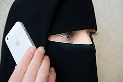 Arab woman wearing traditional black niqab face covering using iPhone