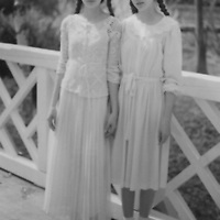 Teenage female twins standing together holding hands wearing white dresses