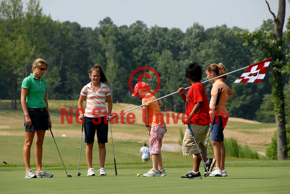 Golf campers play a round at the Lonnie Poole Golf Course. PHOTO BY ROGER WINSTEAD
