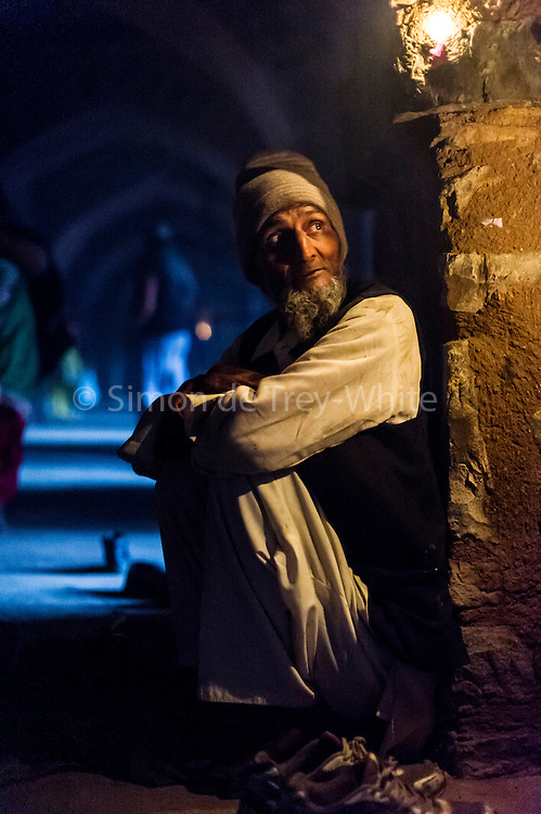 5th February 2015, New Delhi, India. A man who watches over peoples shoes while they pray sits in the catacombs of Feroz Shah Kotla in New Delhi, India on the 5th February 2015 <br /> <br /> PHOTOGRAPH BY AND COPYRIGHT OF SIMON DE TREY-WHITE a photographer in delhi. + 91 98103 99809. Email:simon@simondetreywhite.com<br /> <br /> People have been coming to Firoz Shah Kotla to leave written notes and offerings for Djinns in the hopes of getting wishes granted since the late 1970's. Jinn, jann or djinn are supernatural creatures in Islamic mythology as well as pre-Islamic Arabian mythology. They are mentioned frequently in the Quran  and other Islamic texts and inhabit an unseen world called Djinnestan. In Islamic theology jinn are said to be creatures with free will, made from smokeless fire by Allah as humans were made of clay, among other things. According to the Quran, jinn have free will, and Iblīs abused this freedom in front of Allah by refusing to bow to Adam when Allah ordered angels and jinn to do so. For disobeying Allah, Iblīs was expelled from Paradise and called &quot;Shayṭān&quot; (Satan).They are usually invisible to humans, but humans do appear clearly to jinn, as they can possess them. Like humans, jinn will also be judged on the Day of Judgment and will be sent to Paradise or Hell according to their deeds. Feroz Shah Tughlaq (r. 1351&ndash;88), the Sultan of Delhi, established the fortified city of Ferozabad in 1354, as the new capital of the Delhi Sultanate, and included in it the site of the present Feroz Shah Kotla. Kotla literally means fortress or citadel.