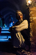 "5th February 2015, New Delhi, India. A man who watches over peoples shoes while they pray sits in the catacombs of Feroz Shah Kotla in New Delhi, India on the 5th February 2015 <br /> <br /> PHOTOGRAPH BY AND COPYRIGHT OF SIMON DE TREY-WHITE a photographer in delhi. + 91 98103 99809. Email:simon@simondetreywhite.com<br /> <br /> People have been coming to Firoz Shah Kotla to leave written notes and offerings for Djinns in the hopes of getting wishes granted since the late 1970's. Jinn, jann or djinn are supernatural creatures in Islamic mythology as well as pre-Islamic Arabian mythology. They are mentioned frequently in the Quran  and other Islamic texts and inhabit an unseen world called Djinnestan. In Islamic theology jinn are said to be creatures with free will, made from smokeless fire by Allah as humans were made of clay, among other things. According to the Quran, jinn have free will, and Iblīs abused this freedom in front of Allah by refusing to bow to Adam when Allah ordered angels and jinn to do so. For disobeying Allah, Iblīs was expelled from Paradise and called ""Shayṭān"" (Satan).They are usually invisible to humans, but humans do appear clearly to jinn, as they can possess them. Like humans, jinn will also be judged on the Day of Judgment and will be sent to Paradise or Hell according to their deeds. Feroz Shah Tughlaq (r. 1351–88), the Sultan of Delhi, established the fortified city of Ferozabad in 1354, as the new capital of the Delhi Sultanate, and included in it the site of the present Feroz Shah Kotla. Kotla literally means fortress or citadel."