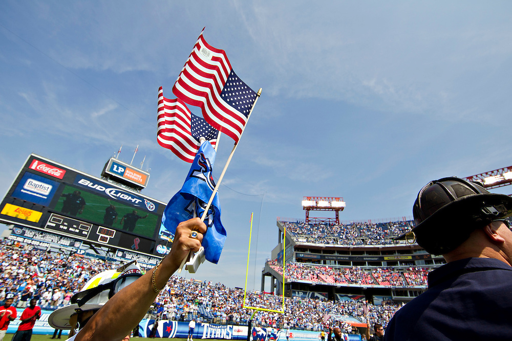 NASHVILLE, TN - SEPTEMBER 18:   Fireman waves the United States and Titans flag before a game between the Tennessee Titans and the Baltimore Ravens at LP Field on September 18, 2011 in Nashville, Tennessee.  The Titans defeated the Ravens 26 to 13.  (Photo by Wesley Hitt/Getty Images) *** Local Caption ***