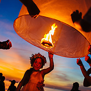 A young girl launches a paper lantern at a destination wedding in Phuket, Thailand.