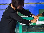07 AUGUST 2016 - BANGKOK, THAILAND:  A woman locks a ballot box before the polls open at a polling place at Wat That Thong in Bangkok. Thais voted Sunday in the referendum to approve a new charter (constitution) for Thailand. The new charter was written by a government appointed panel after the military coup that deposed the elected civilian government in May, 2014. The charter referendum is the first country wide election since the coup.      PHOTO BY JACK KURTZ
