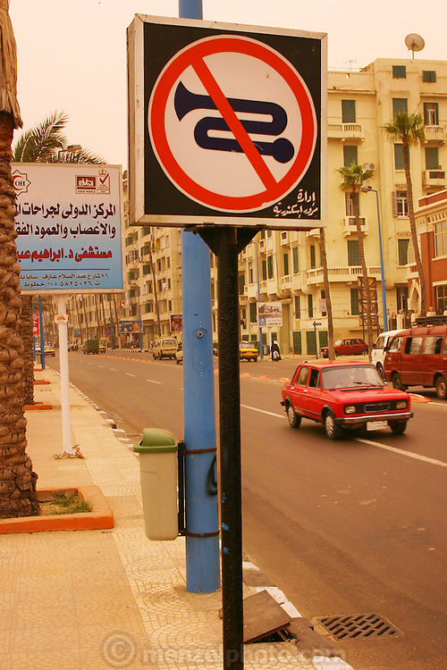 "A ""no-honking"" sign in downtown Alexandria, Egypt during a sandstorm. The yellow-orange light is from the sand in the sky filtering the sunlight."