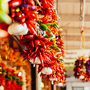 Peppers hang in a covered area of a farmer's market in Seattle, Washington.