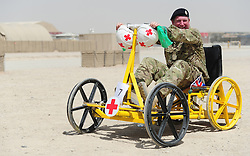 © Licensed to London News Pictures. 18/08/2011. Bastion, Afghanistan. Staff Sergeant Dave Corden with one of the many make your own Karts that took part in a Kart race in Camp Bastion today . Staff Sergeant Corden organised the event to raise money for Kart Force - a UK based charity that provides modified karts for injured troops.  Photo credit : Sergeant Alison Baskerville/LNP