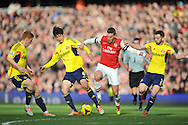 Arsenal's Lukas Podolski using his stength against Sunderland's Ki Sung-Yueng and Phil Bardsley during Barclays Premier League , Arsenal v Sunderland at the Emirates Stadium in London, England on Saturday 22nd Feb 2014.<br /> pic by John Fletcher, Andrew Orchard sports photography.