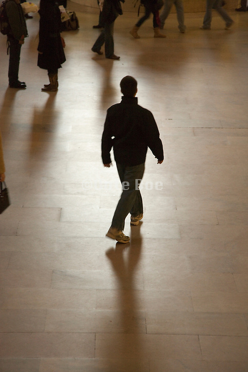 silhouette of a man walking in a passenger terminal