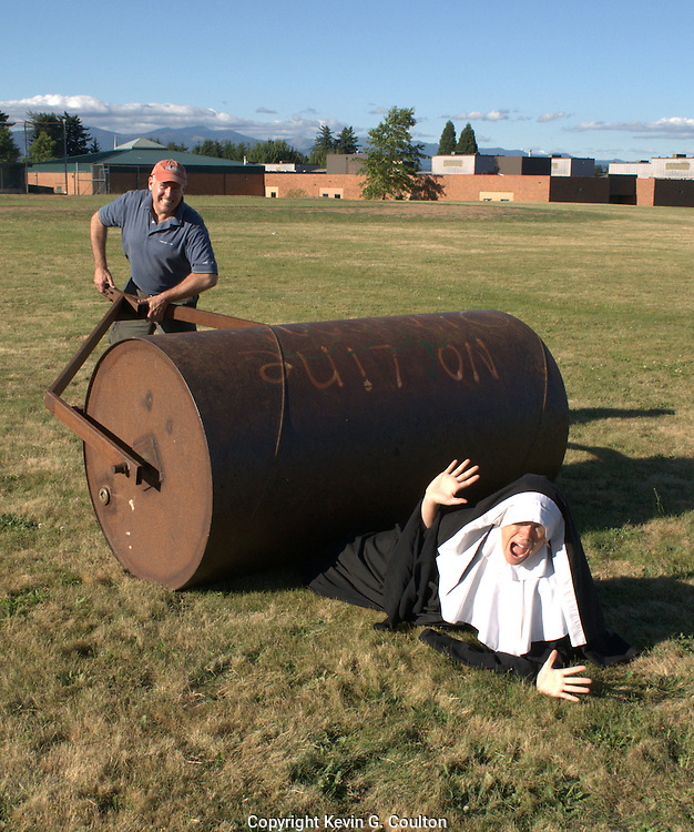 "Humorous photograph of a man pushing a large roller over a nun visually depicting the saying ""Holy roller!"""