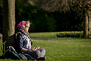 After a weekend of large numbers of Britons leaving London for holiday resorts and coastal beauty spots, and crowding into the capital's parks, the UK government is considering further restrictions of movement in public places to help social distancing during the Coronavirus pandemic. Some public green spaces have been closed by their own local authority but most, such as Ruskin Park in south London, are still open. Kerry is a local musician and broadcaster and sits meditating under a tree listening to music ideas for her podcast, on 23rd March 2020, in London, England.