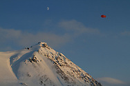 Moon and tethered weather blimp hover above the international science village of Ny-Alesund on Spitsbergen island in Kongsfjorden; Svalbard, Norway.