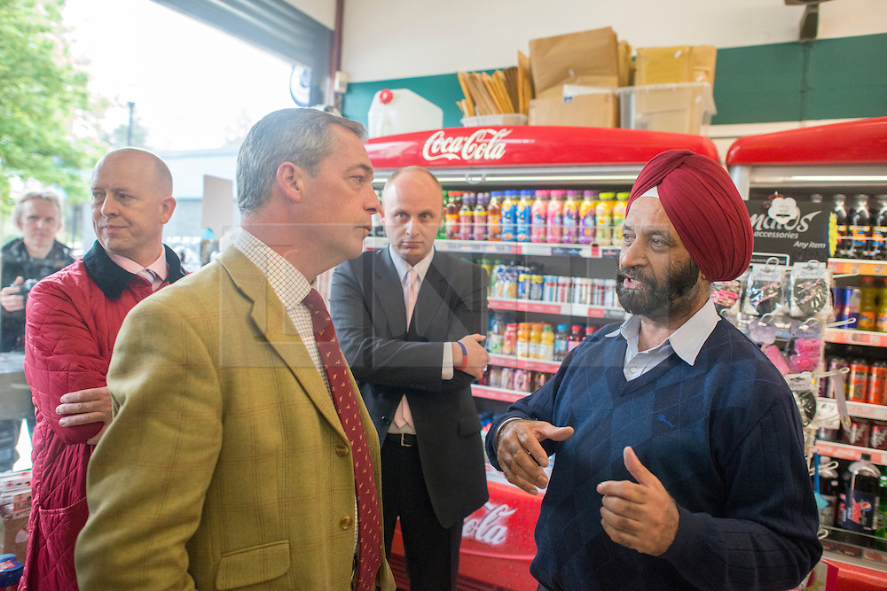 © Licensed to London News Pictures. 29/04/2014. Slough, UK. Nigel Farage meets with local shopkeeper Hervinder Dial over concerns about his shop. NIGEL FARAGE leader of UKIP in Slough today 29 April 2014 to congratulate local activists on more than doubling the candidates the party will field in local elections. Photo credit : Stephen Simpson/LNP