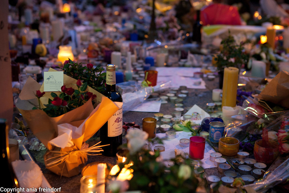 """Paris Terrorist Attacks, people Mourning in front of Bar """"Le Carillon"""" and Restaurant """"Le Petit Cambodge"""", where 15 people died from Kalashnikov shooting on 13/11/15, red roses, wine."""