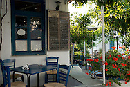 Traditional wooden chairs and red geraniums outside a taverna in Apollonia, Sifnos, The Cyclades, The Greek Islands, Greece, Europe