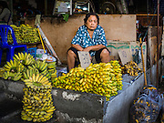 "12 JANUARY 2016 - BANGKOK, THAILAND: A banana vendor in Khlong Toey Market in Bangkok. Khlong Toey (also called Khlong Toei) Market is one of the largest ""wet markets"" in Thailand. The market is located in the midst of one of Bangkok's largest slum areas and close to the city's original deep water port. Thousands of people live in the neighboring slum area. Thousands more shop in the sprawling market for fresh fruits and vegetables as well meat, fish and poultry.         PHOTO BY JACK KURTZ"