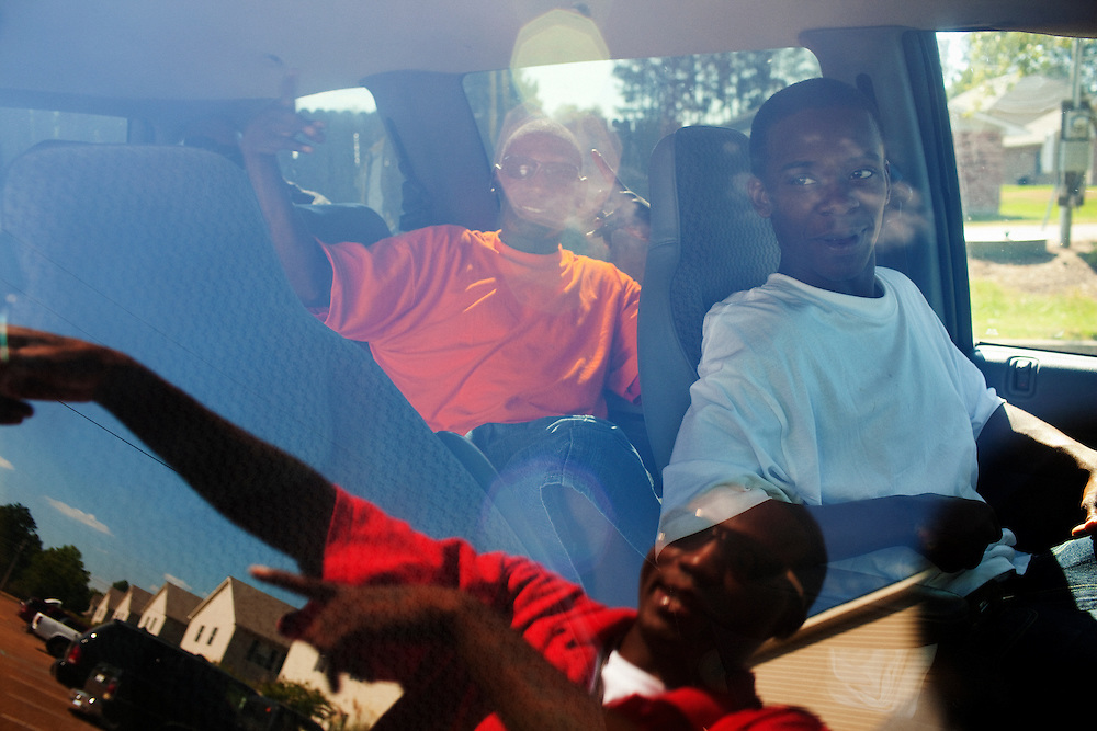 Winky Williams (in reflection), Robert Pritchett (R) and a friend load into a van on the fourth of July in the Baptist Town neighborhood of Greenwood, Mississippi before driving out to the lake in Grenada on Sunday, July 4, 2010.