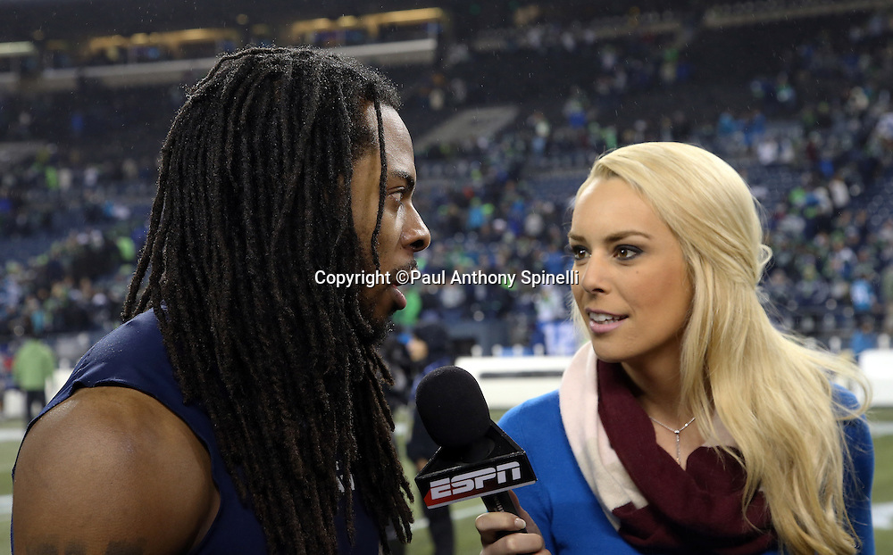 Seattle Seahawks cornerback Richard Sherman (25) does a postgame television interview with an ESPN sideline reporter on the field after the NFL week 19 NFC Divisional Playoff football game against the Carolina Panthers on Saturday, Jan. 10, 2015 in Seattle. The Seahawks won the game 31-17. ©Paul Anthony Spinelli