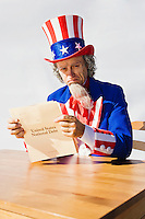 Portrait of Uncle Sam sitting at a table with tears in his eyes while reading the National Debt.