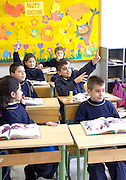 LEBANON, BEIRUT:  School classroom with children in uniforms participating in discussions about reading and raising hand to answer questions.