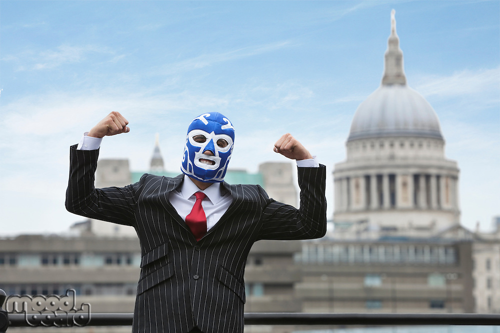 Young businessman flexing muscles while wearing wrestling mask with St. Paul's Cathedral building in the background