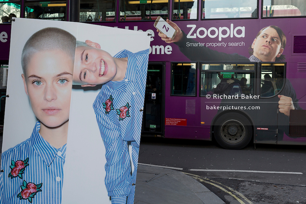 "A bus ad for property website Zoopla passes the London Fashion Week in the Strand, on 17th Febriary 2017, in London, England, United Kingdom. London Fashion Week is a clothing trade show held in London twice each year, in February and September. It is one of the ""Big Four"" fashion weeks, along with the New York, Milan and Paris. The fashion sector plays a significant role in the UK economy with London Fashion Week alone estimated to rake in £269 million each season. The six-day industry event allows designers to show their collections to buyers, journalists and celebrities and also maintains the city's status as a top fashion capital."