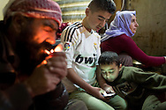 18/02/15 --TANJERO, IRAQ: Sa&iuml;d lights a cigarette while Ezidiar (9) looks at Serdesht's (13) phone and Ghazal watches television.<br /> <br /> The family of Yezidis, displaced from Sinjar, live next to an oil refinery in the Kurdish Region of Iraq. The young men run the refinery 24 hours a day with little to no safety equipment. Reporting for this article was supported by a grant from the Pulitzer Center on Crisis Reporting