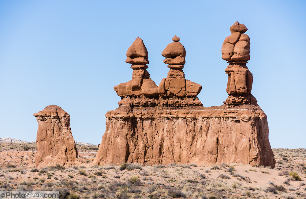 Three Sisters hoodoos. Admire fanciful hoodoos, mushroom shapes, and rock pinnacles in Goblin Valley State Park, in Emery County between the towns of Green River and Hanksville, in central Utah, USA. The Goblin rocks eroded from Entrada Sandstone, which is comprised of alternating layers of sandstone (cross-bedded by former tides), siltstone, and shale debris which were eroded from former highlands and redeposited in beds on a former tidal flat. As part of the Colorado Plateau, the San Rafael Swell is a giant dome-shaped anticline of rock (160-175 million years old) that was pushed up during the Paleocene Laramide Orogeny 60-40 million years ago. Since then, infrequent but powerful flash floods have eroded the sedimentary rocks into valleys, canyons, gorges, mesas, and buttes.