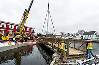 Crews work to set the metal footbridge in place at Perley Canal and Jewett Brook behind Church Street on Thursday morning.  (Karen Bobotas/for the Laconia Daily Sun)